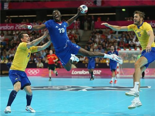 Luc Abalo of France jumps to shoot while Dalibor Doder and Jonas Larholm of Sweden can only watch on during the Men's Handball preliminaries group A match between France and Sweden.
