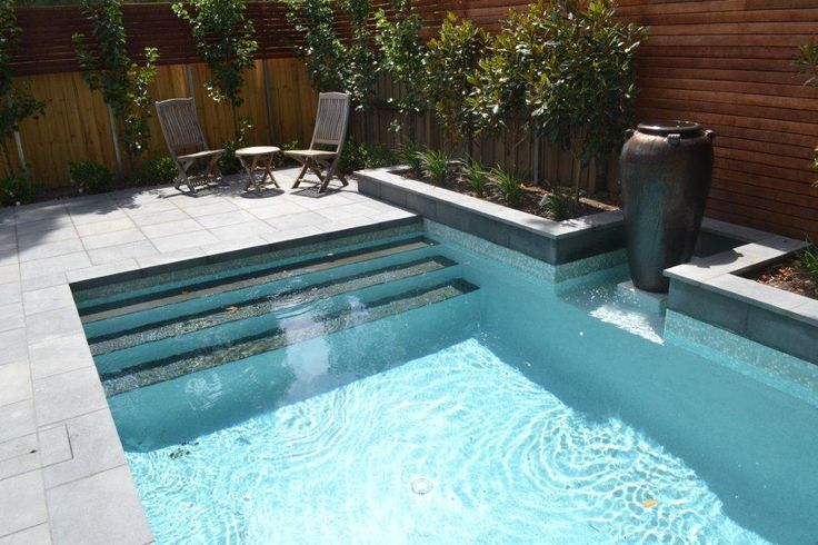 Getting ready for summer? This beautiful pool surround features #Bluestone tiles around the raised garden bed, #pool #surrounds and even the steps into the pool.