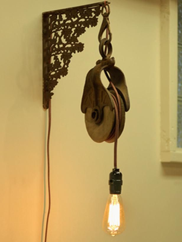 Upcycled Lamps and Lighting Ideas: A salvage-yard bracket and pulley are joined with an Edison bulb to make a rustic wall sconce. Design by Joanne Palmisano.  From DIYnetwork.com