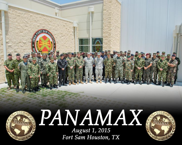 A large group of soldiers dressed in combat fatigues stand together in four rows in front of a building.