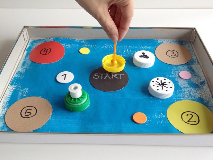 Create your own recycled bottle cap spinning tops and game boards!