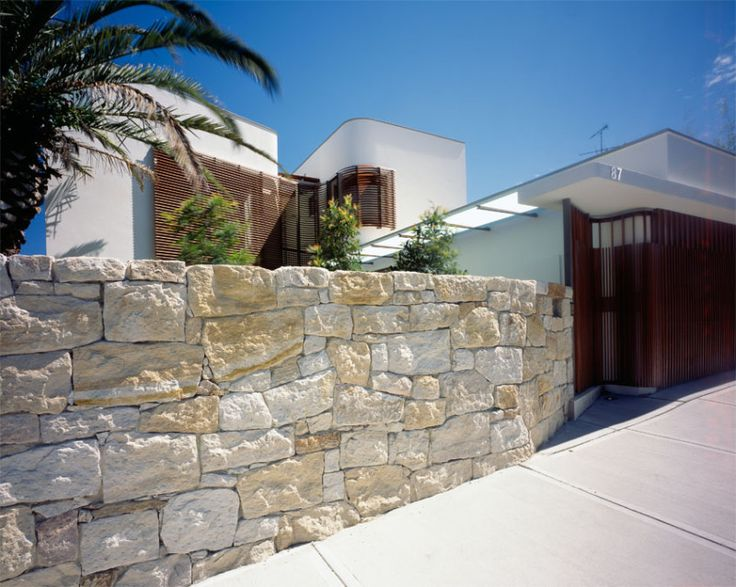 Sandstone walling screens the house from the street and echoes its beachside location | © Blain Crellin