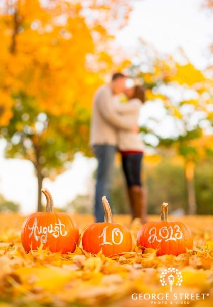 NOAH'S Event Venue | Photo by George Street Photo - Autumn engagement photo. Great picture for your Save the Date! Write or carve your wedding date on the front of Pumpkins.