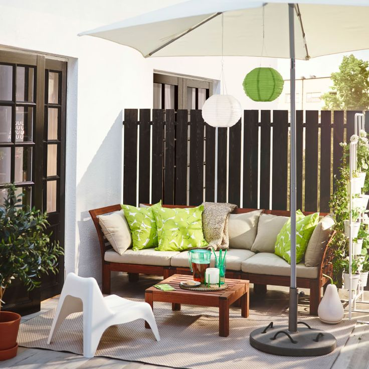 A sunny patio with a brown stained outdoor three-seat sofa filled with beige and green cushions. Shown with a low table and a children's easy chair in white plastic.