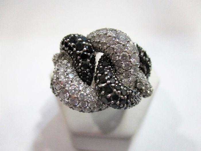 Gouden cocktail ring met zwarte en witte diamanten Zeer moderne witgoud ring met een gevlochten schacht met een patroon gemaakt van witte en zwarte diamanten.De diamanten zijn alle natuurlijke en ronde briljant gesneden. De witte zijn G kleur en helderheid van de VS.Er zijn 87 witte diamanten en ze variëren in grootte van 0005 ct tot 0.06 ct voor een totaal van 2 ct.Er zijn 84 zwarte diamanten en ze variëren in grootte van 0005 tot 002 ct voor een totaal van 0.77 ct.De buitenkant van de ring…