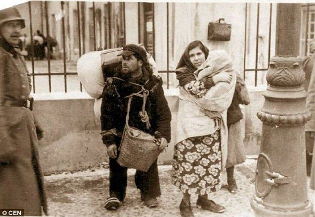 """Lublin. """"A woman holds a child close to her chest alongside a man laden down with belongings as German troops herded residents into cattle trucks to deliver them to their deaths at Belzec or Majdanek."""""""