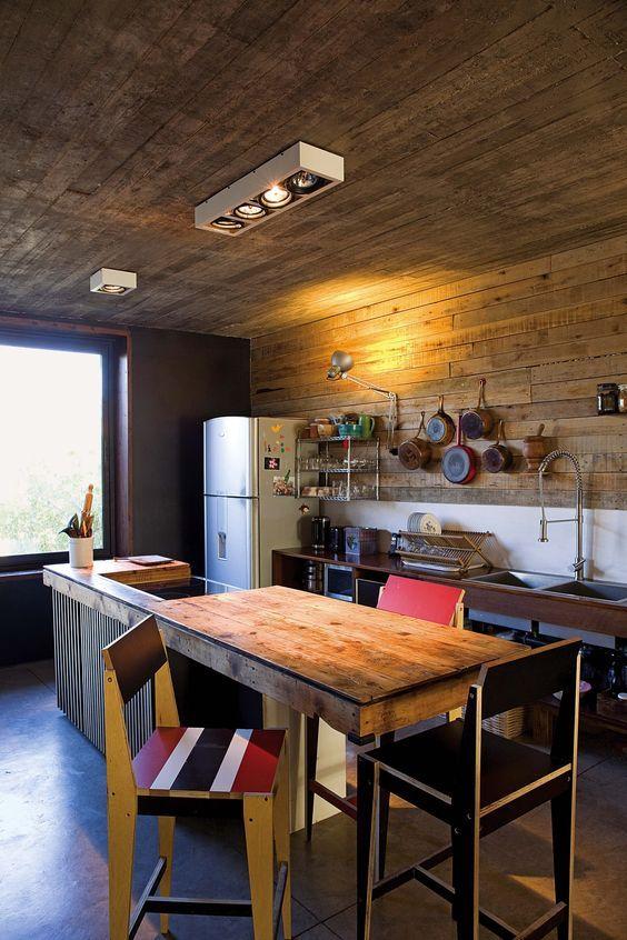 Cocina rústica con barra y revestimiento de madera reciclada en la casa sustentable del Estudio AB. Foto: Javier Csecs