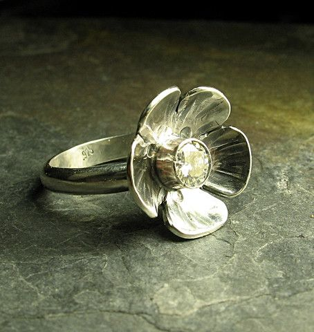 Spring sparkle - glittering moissanite adorns the center of this sweet sterling flower.   .....from Lavender Cottage Jewelry