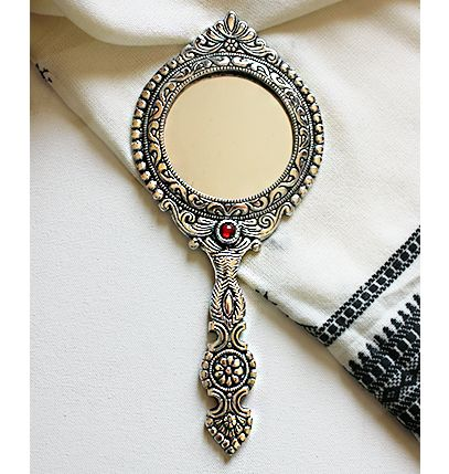 Available at The Indian Weave store/Paypal Accepted.   This is a gorgeous hand held mirror hand crafted from white metal by artisans in West Bengal, India. The Glass is clear with no scratches. Displaying intricate patterns both in the front and back with a red stone in the middle , beautiful floral design and workmanship, this is a delight to own for any woman.