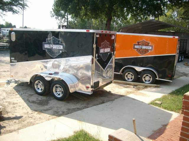 enclosed slant motorcycle package trailer with added Harley stickers.