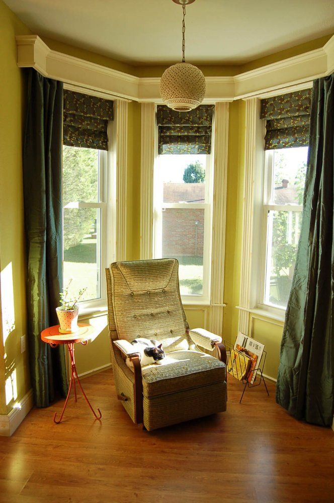 cozy bay window layered wooden cornice drapery and shades