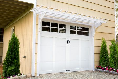 a newly installed pergola above a garage door