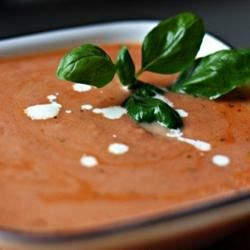 Cooked tomatoes and tomato juice are pureed with fresh basil leaves in this soup thickened with heavy cream.