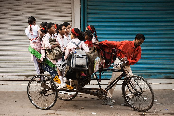 """""""A gaggle of elementary school girls pile into a cycle rickshaw to get their learn on.  In India, education up to a certain point is free (I believe up to middle school). Transportation to education is not. Wake up early enough in the morning and you see a potpourri of methods scraped together to move children to school, often employing techniques that circus clowns would envy."""" - New Delhi, India by Pius Lee (Travel Guy)"""