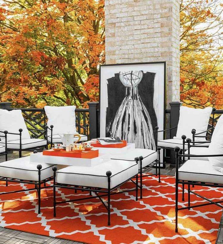 tapis d'extérieur accrocheur en orange à motifs blancs, salon de jardin en fer forgé et cheminée habillée de pierre naturelle