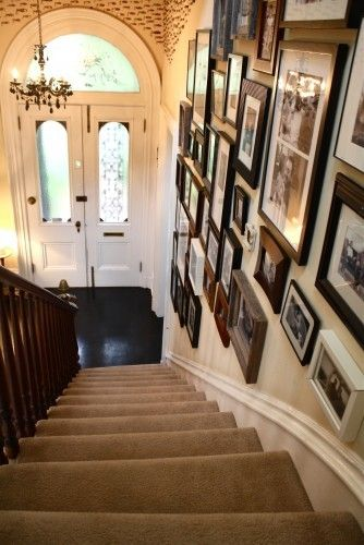 Ok, probably just a bit too much, both in terms of the scale of the foyer (height of ceiling) and the designedness of the picture frames on the wall. But I think the staircase wall being densely-packed with family photos is iconic and essential.
