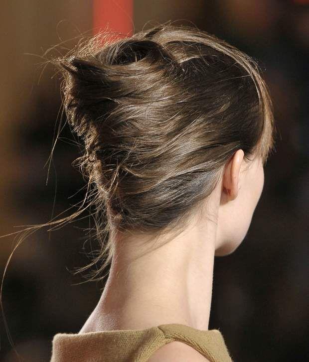 Chignon Banane- Réalisez une raie à l'horizontal, à mi-oreilles, pour séparer l'avant de l'arrière.- Crêpez la base de la mèche inférieure pour donner de la densité puis brossez légèrement pour lisser.- Avec la brosse plate ramenez les cheveux sur un côté et fixez-les avec des épingles curby (ondulées) en suivant une ligne centrale verticale.- En repartant en sens inverse, enroulez la mèche sur elle-même comme une bobine de fil. Fixez avec des épingles neige (en U).- Glissez la partie…