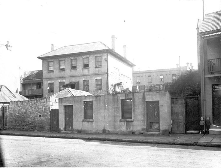 Cumberland & Gloucester Sts, Miller's Point Three-storey rendered sandstone and iron-roofed tenement set back from roadway, with walls and building facades in process of demolition. Passageway to terrace (right) has tall wooden gates, and two children pose next to sandstone entrance steps c1913 NSCA CRS 51, Demolition books, 1900-1949 City of Sydney Archives