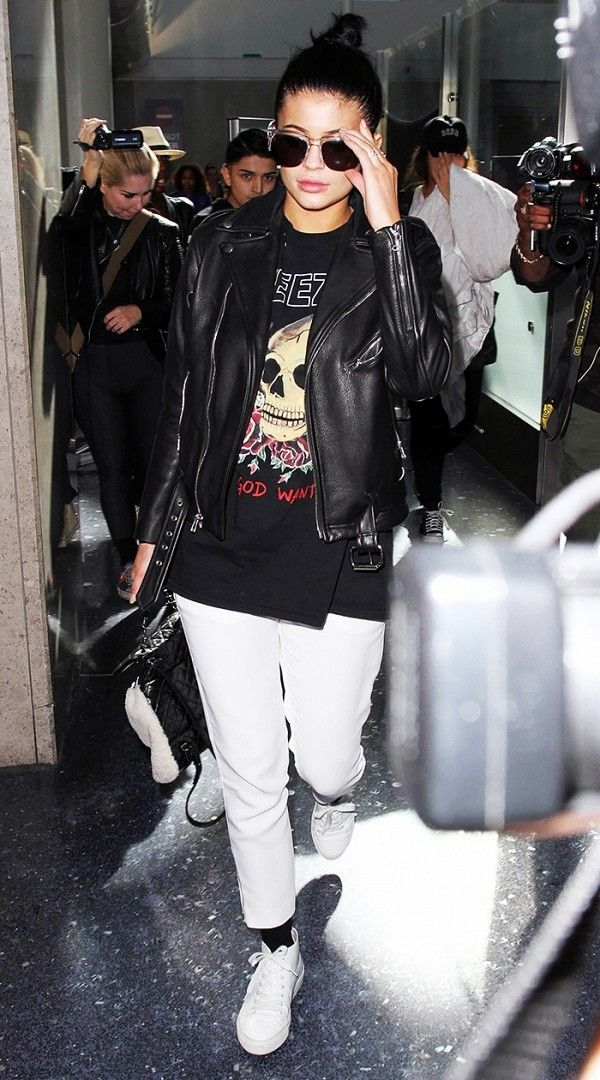 Kylie Jenner styles a graphic tee with a leather biker jacket, stark white jeans, and white sneakers