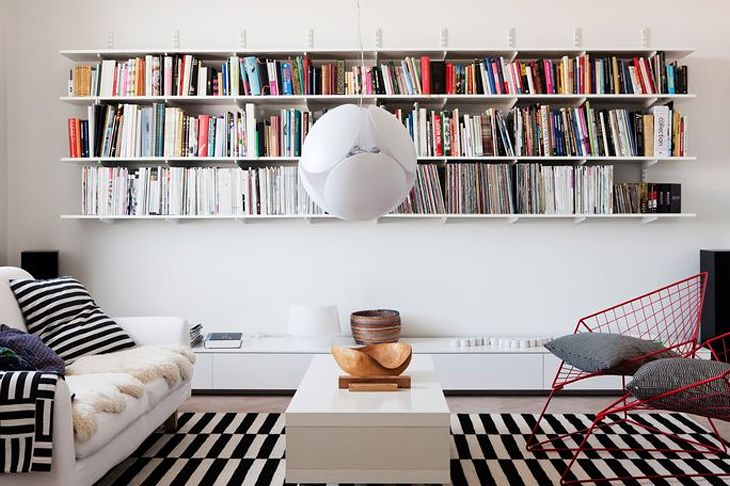 IKEA Stockholm Rand rug, bookshelf, white round lamp, cushions, red metal chair, white coffee table, books