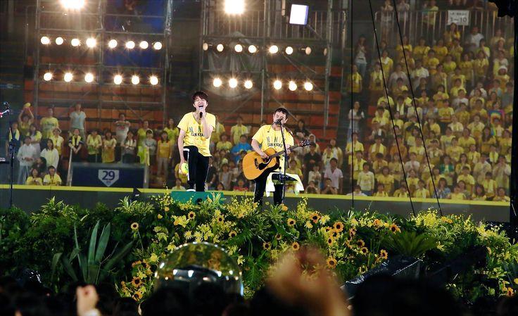 8月15日(土)、16日(日)の2日間にわたり、ゆずが横浜スタジアムで『ゆず 弾き語りライブ 2015 二人参客 in 横浜スタジアム』を開催。同所での単独有料ライヴは2000年の『夏の野球場ツアー 2000 満員音(楽)礼~熱闘! Bomb 踊り~』以来15年ぶりとなり、1日目は「緑の日」、2日目は「黄色の日」とそれぞれにテーマを設け、客席は各日のテーマカラーのTシャツなどに身を包んだ観客で埋め尽くされた。  スタンドもアリーナも黄色に染まった2日目。まずは、ゆずのライヴの恒例「ラジオ体操第一」で観客もスタッフも一緒になって身体を温めてから、マーチングバンドによるファンファーレ~「夏色」の演奏で華々しく幕を開けた。  本物の草花で...