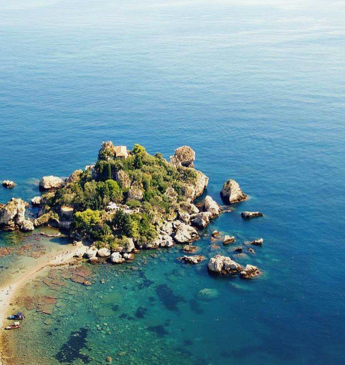 A thin rocky beach leads you to the charming nature reserve of Isola Bella near #taormina  Travellector takes you to the gems of Sicily's Catania and its surroundings