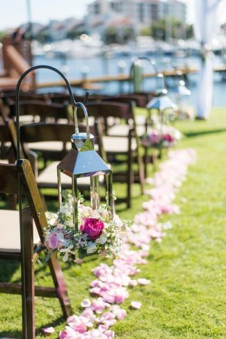 Lanterns filled with flowers hanging from a shepherd's hooks along a ceremony aisle in Florida