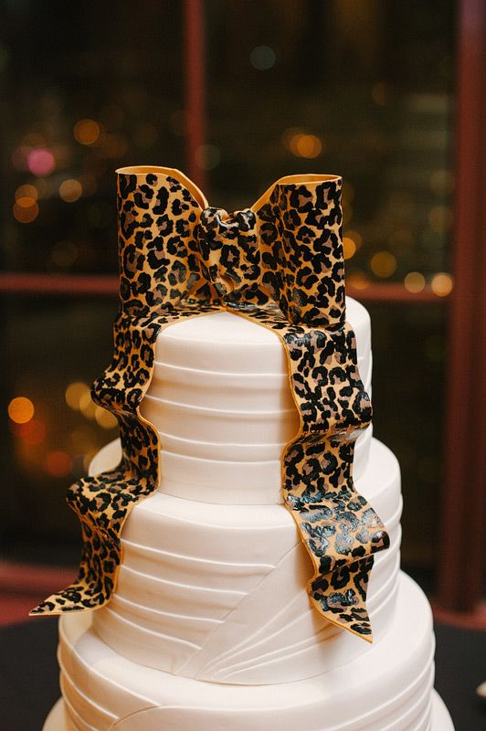 White wedding cake with edible leopard print bow.