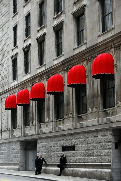 Red awnings add a bold pop of color to a traditional building façade.