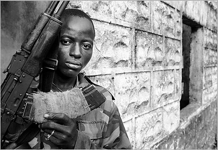 Sierra Leone Civil War (1991-2002) Henry, a teenaged Revolutionary United Force rebel solider, brandishes his weapon June 9, 2001 in the town of Koindu, Sierra Leone.