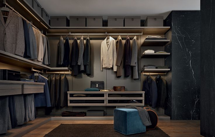 Ubik walk-in closet with visone mat lacquered wall panels, shelves and hanging chest of drawers in cenere oak melamine. Base in cenere oak melamine with plinth in piombo painted aluminium. Play pouf with 58 danubio Persia removable velvet covering.