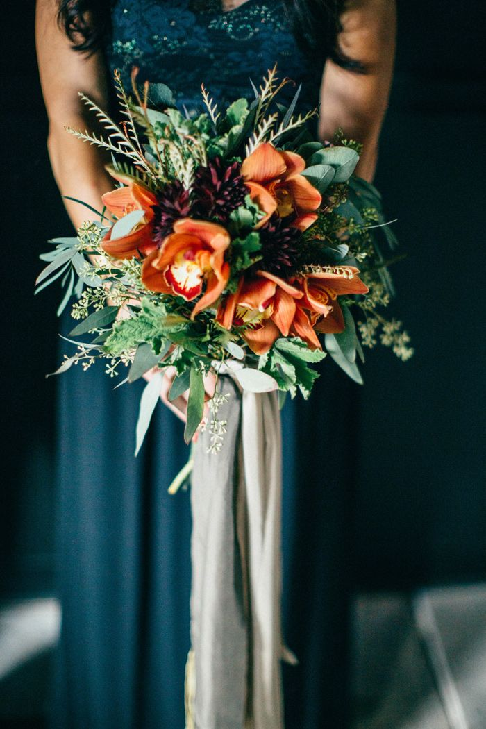 Lovely autumnal rustic bouquet with orchids and dahlia with dark teal bridesmaid dress