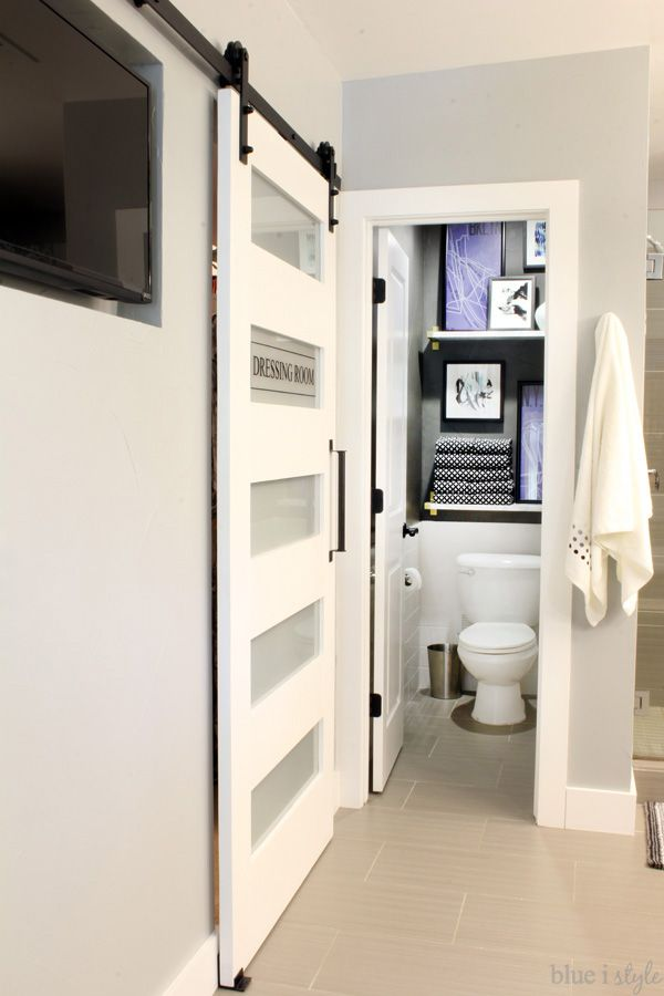 """This """"dressing room"""" barn door separates the master bathroom and closet without taking up valuable floor space. It slides right in front of the television recessed into the wall."""