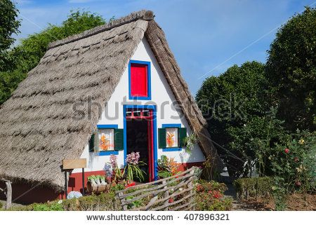 Traditional colored houses at Santana village, Madeira Island. Typical triangular houses with straw roof, red door and small windows with shutters, originally built by local farmers.