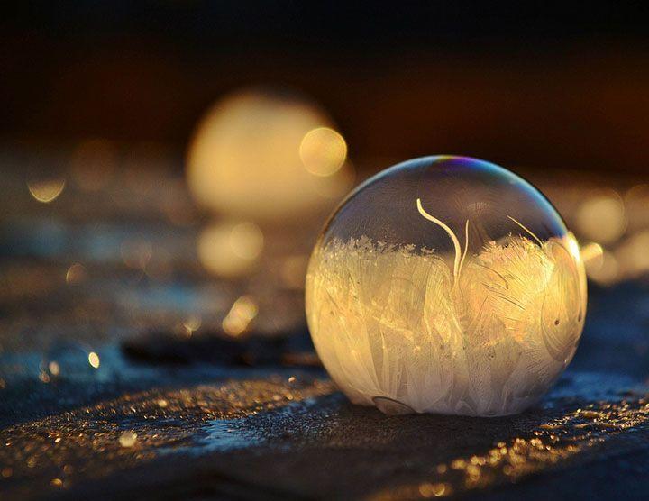 Un petit garçon souffle des bulles de savon qui se cristallisent dans le froid…