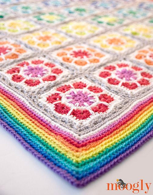"""Last week I shared my pattern for the Mini Magic Mandala Squares - a great 6"""" afghan block pattern made in worsted weight yarn. This week, I take that pattern, change the yarn size, add an easy join as you go technique, and a big bold border… and present the Magic Rainbow Baby Blanket free crochet pattern!"""