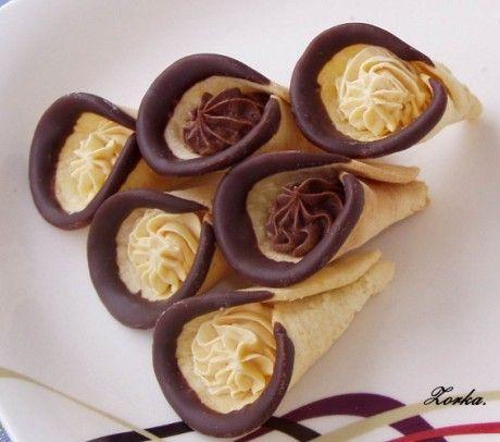 medové kornoutky s karamelovým krémem Medové kornoutky plněné šlehačkou * 125 g hladké mouky * 50 g moučkového cukru * 1/2 polévkové lžíce mléka * 75 g medu * 1 žloutek * špetka jedlé sody Náplň: * 125 ml šlehačky * 1/2 pytlíku ztužovače šlehačky * čokoládová poleva