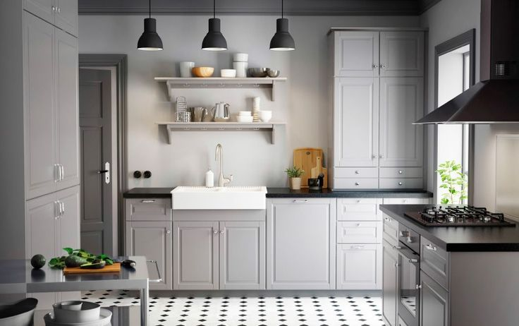 A country kitchen with grey inset doors, black worktops and chrome handles and knobs