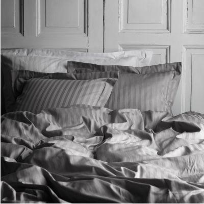 Gråa sängkläder under det rosa o krämiga