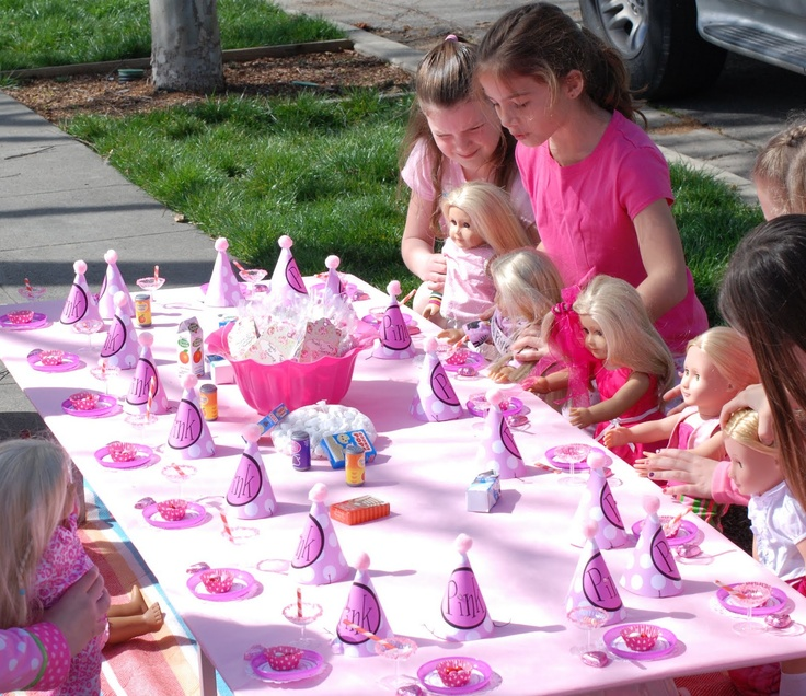 Girls setting up their dolls at their own table.