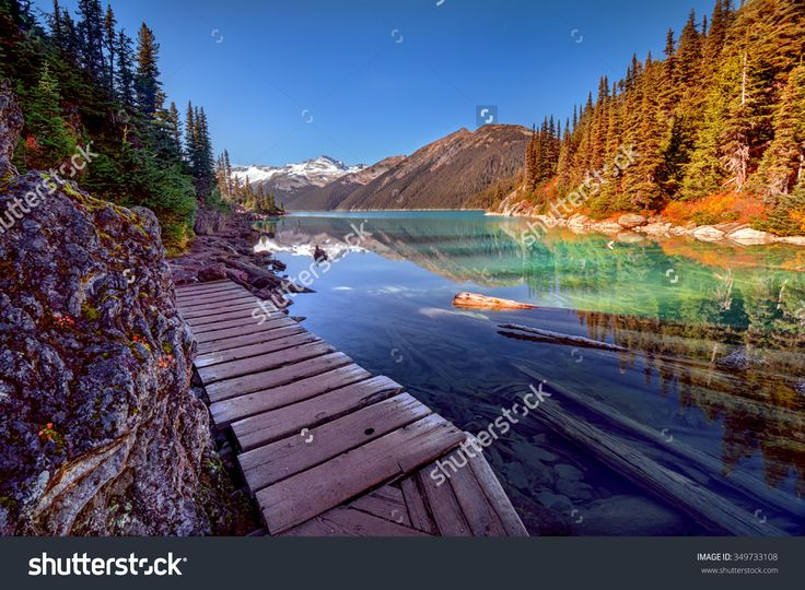 Wooden Walkway Along The Glacial Lake, With Pine Trees And ...