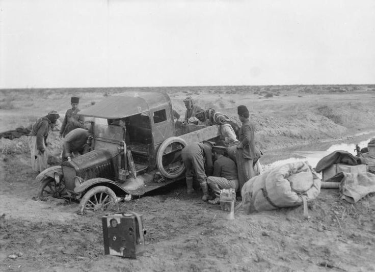 Car belonging to Mr Ariel Varges, British official cameraman, stuck in the mud. Mesopotamia, probably 1918. Note the Moy & Bastie cinecamera in the left foreground.
