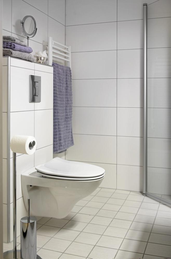 Et dusjkabinett med innfellbare dører fra Gustavsberg sparer på plassen i dette lille rommet. Innbyggingssisternen er fra Grohe, den hvite håndklevarmeren fra LVI Norge og stativet med toalettbørste og dorullholder fra Comfort.