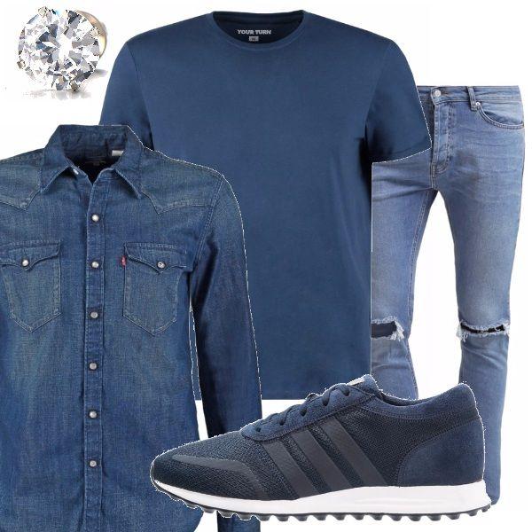 Stile sportivo e casual con i pantaloni strappati sulle ginocchia, maglietta basic e camicia di jeans, sneakers tutto nella tonalità del blu. Dettaglio prezioso l'orecchino a lobo.