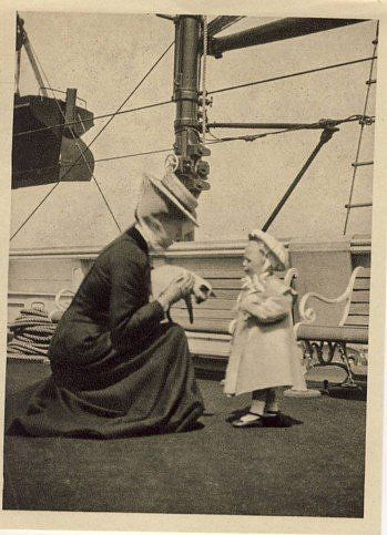 Princess Victoria, daughter of Edward VII & Queen Alexandra, holding a siamese cat on the royal yacht about 1914.