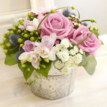 This is delicate and sophisticated. Blooms clustered together with berries and other accents.
