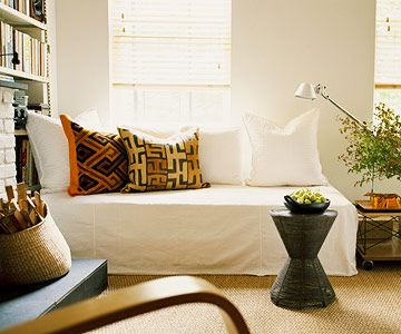 A twin bed is used as a couch in this living room, covered with a canvas drop cloth.  Easily converts to a guest bed!