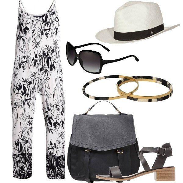 Comoda jumpsuit con spalline strette e scollo profondo. Comodi sandali con fibbia e zainetto. Il cappello e gli occhiali a lente scura donano misteriosità all'outfit. Bracciali rigidi.