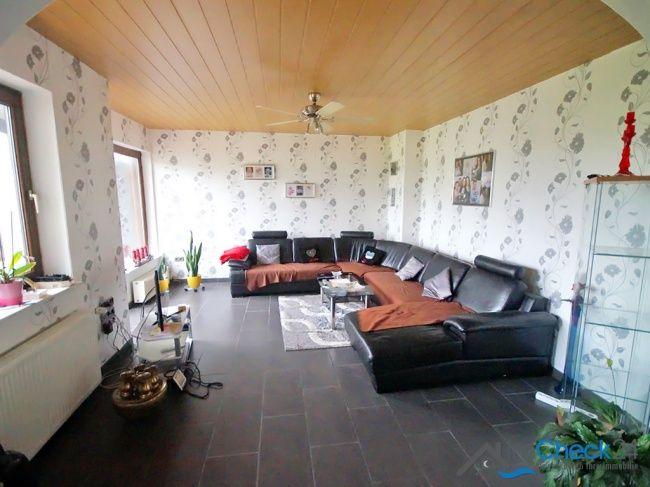 Langgezogenes Wohnzimmer mit modern gehaltenen Bodenfliesen und Zugang zum Gartenbereich.