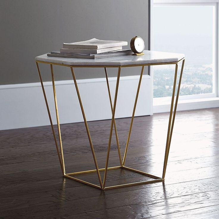Table inspired by the Japanese art of origami. Made of solid marble with a faceted, open base of gold-finished metal.